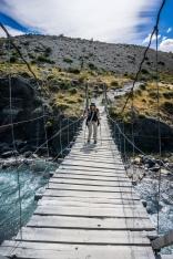 Michelle crosses a swing bridge.